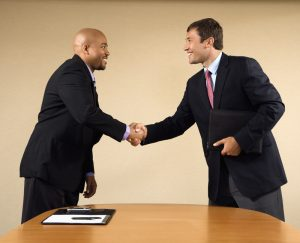 Two businessmen in suits shaking hands and smiling.